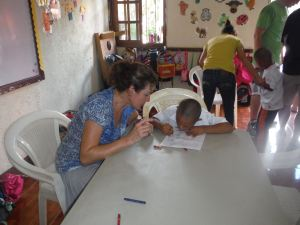 A team member working with a child in the Agape program to complete rotation stations based around the gifts God has given us.